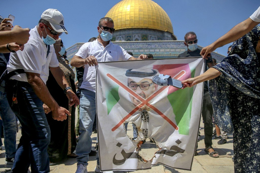 Palestinian protesters prepare to tear apart a portrait of Abu Dhabi Crown Prince Mohammed bin Zayed at al-Aqsa compound on 14 August (AFP)