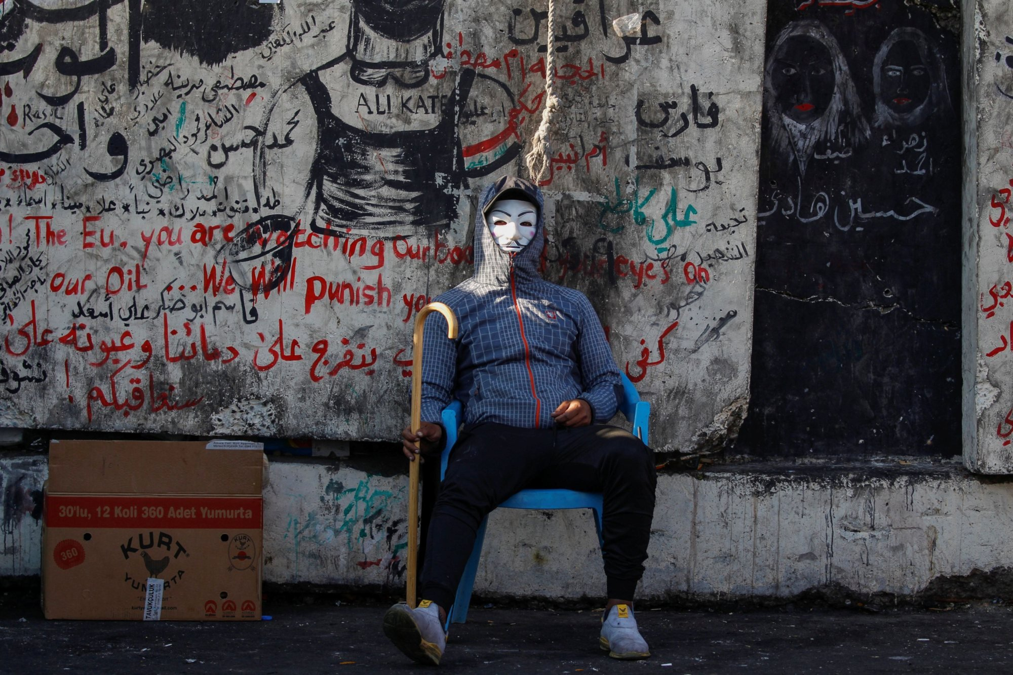 An Iraqi demonstrator sits wearing a mask during the ongoing anti-government protests in Baghdad, Iraq on 22 November 2019 (Reuters)