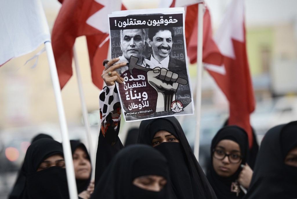 Bahrainis hold up a poster bearing portraits of Rajab and Abdulhadi Alkhawaja during a protest west of Manama in 2015 (AFP)