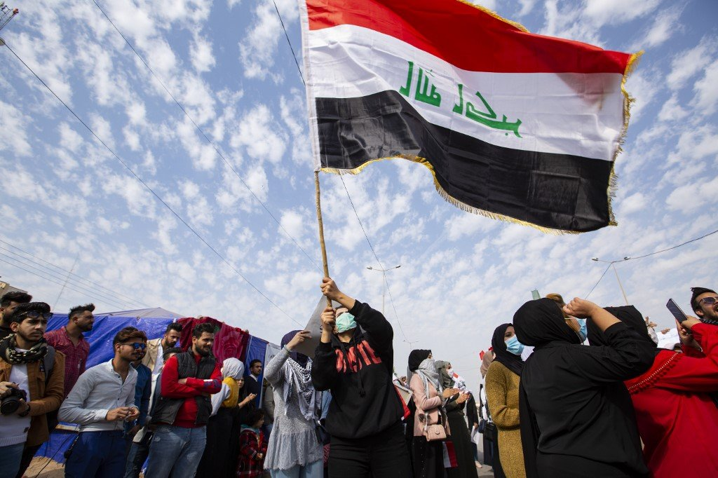 An Iraqi student waves the national flag during an anti-government demonstration in Basra on 31 December (AFP)