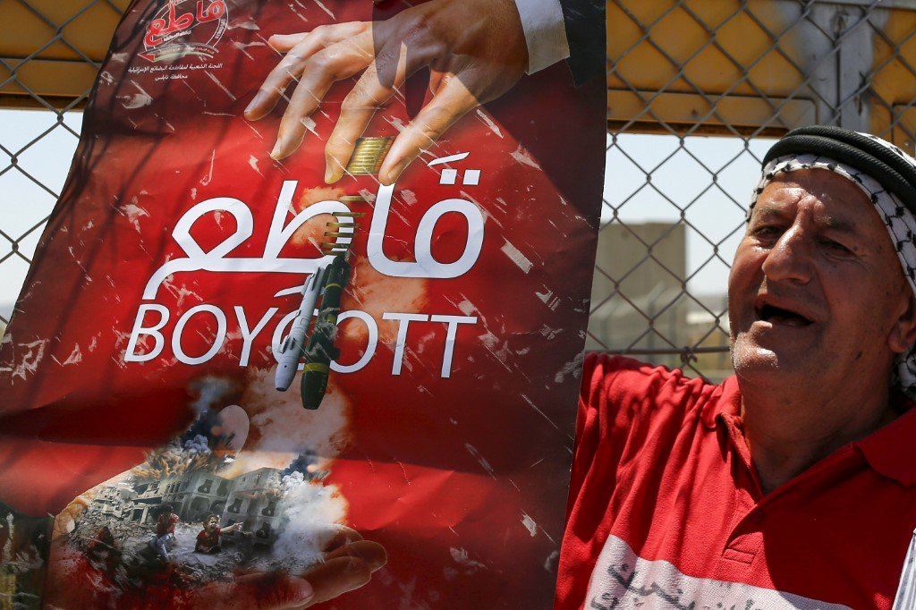A Palestinian man demonstrates in support of BDS near Ramallah on 6 August (AFP)