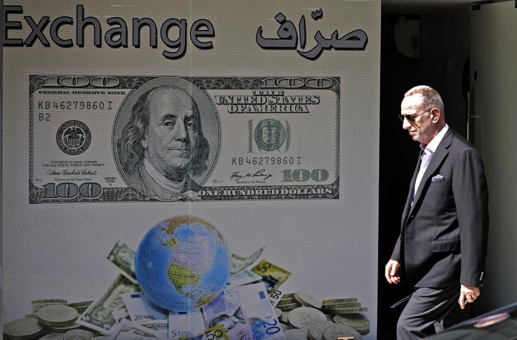 A man walks past a money exchange company in Beirut on 1 October (AFP)