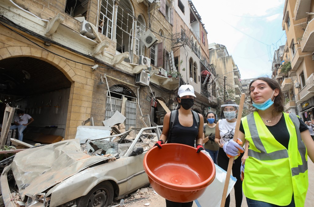 Volunteers arrive in Beirut's Gemmayzeh neighbourhood to clear debris on 6 August (AFP)