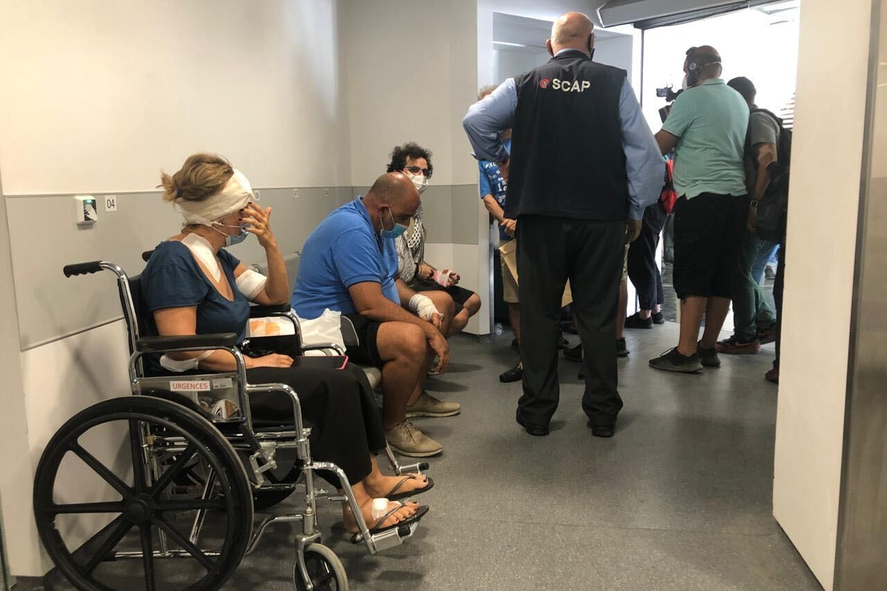 Patients with visible injuries sit down after being treated at Hotel Dieu de France.