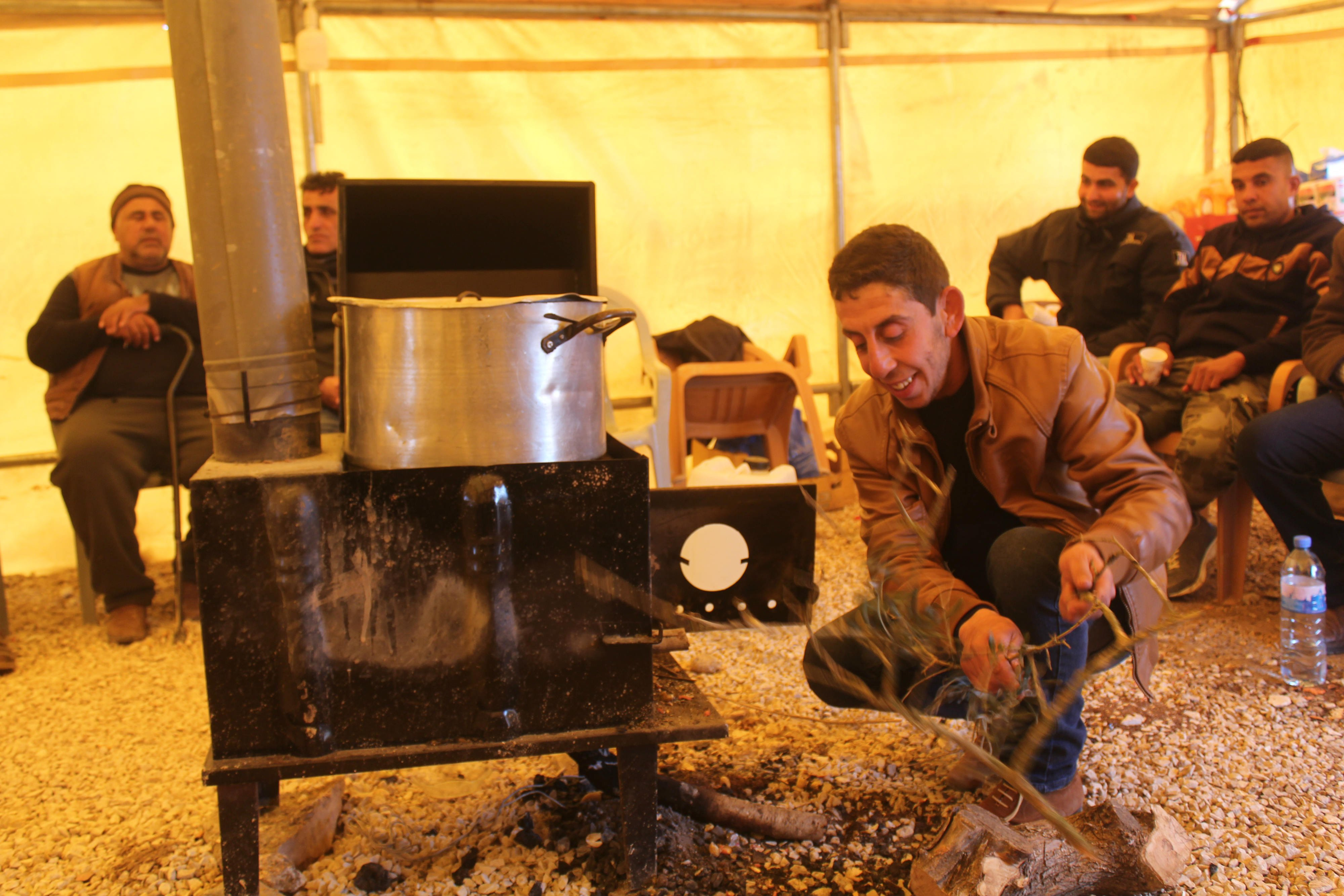 Inside the tent, volunteers make Freekeh soup, a popular Palestinian food usually prepared in the winter as it provides the body with energy and warmth (MEE/Shatha Hammad)