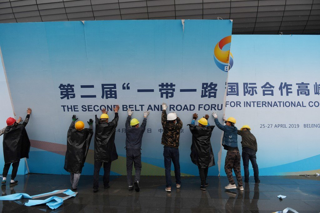 Workers take down a Belt and Road Forum panel outside the venue of the forum in Beijing in April 2019 (AFP)