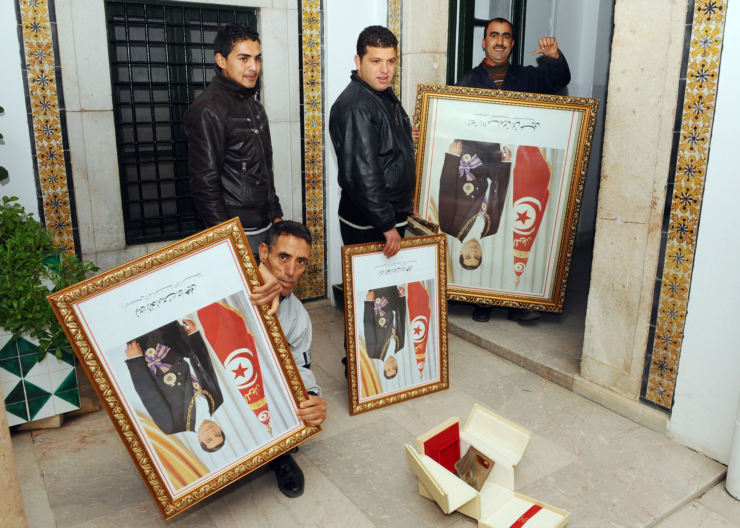 Tunisian employees of the Prime ministry remove portraits of Ben Ali on 17 January 2011, three days after he fled the country following a month of protests (AFP)