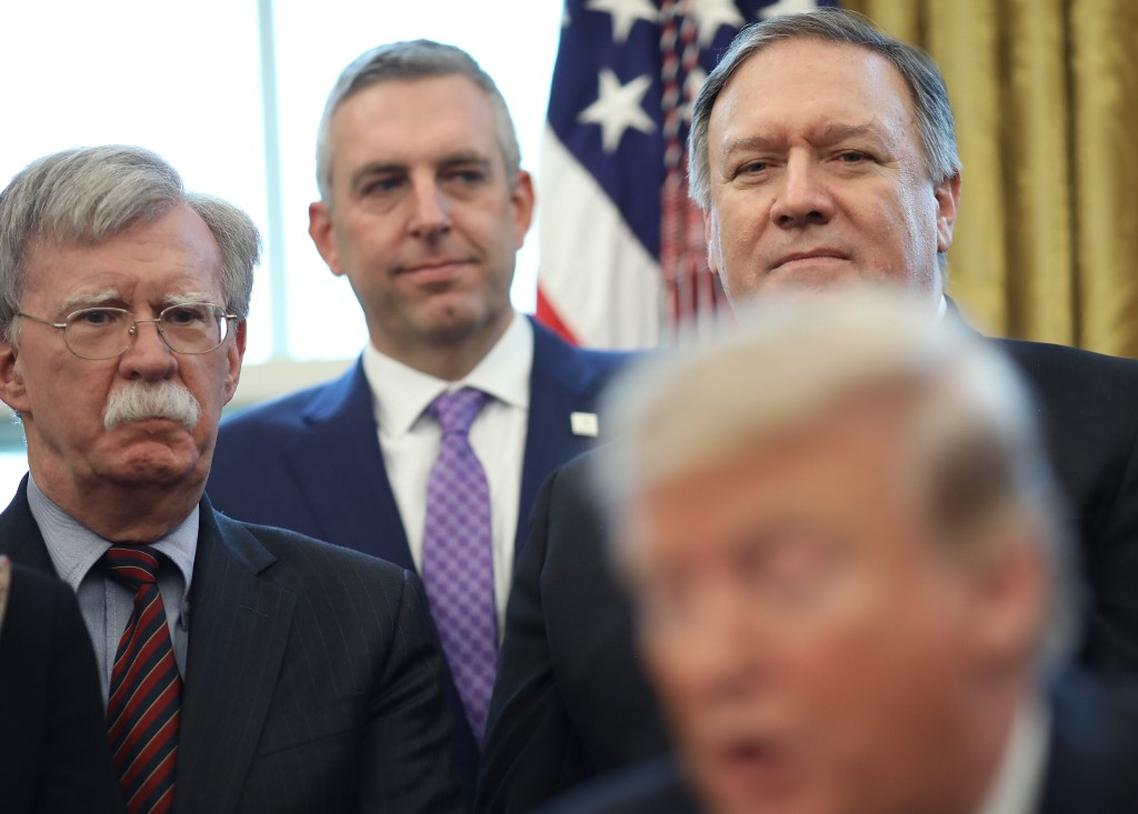 US National Security Adviser John Bolton and Secretary of State Mike Pompeo listen as Trump speaks in the Oval Office in Washington on 7 February (AFP)