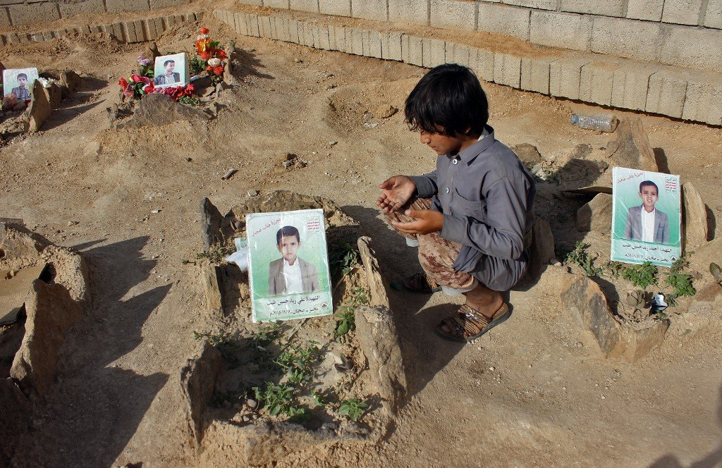 A Yemeni child recites a prayer by the graves of schoolboys who were killed while on a bus that was hit by a Saudi-led coalition air strike on the Dahyan market in August, at a cemetery in the Huthi rebels' stronghold province of Saada on September 4, 2018.