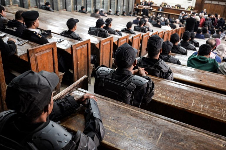 Members of the Egyptian security forces sit in a Cairo courthouse on 2 December (AFP)