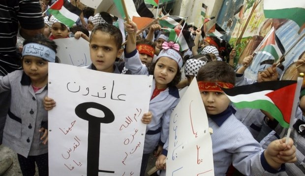 Palestinian children hold up pictures of keys, symbolising the homes they lost (AFP)