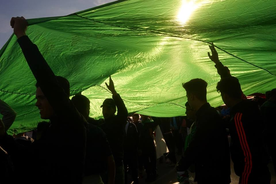 Protestors carry an Algerian flag over the heads during a recent demonstration (Houari Bouchenak)