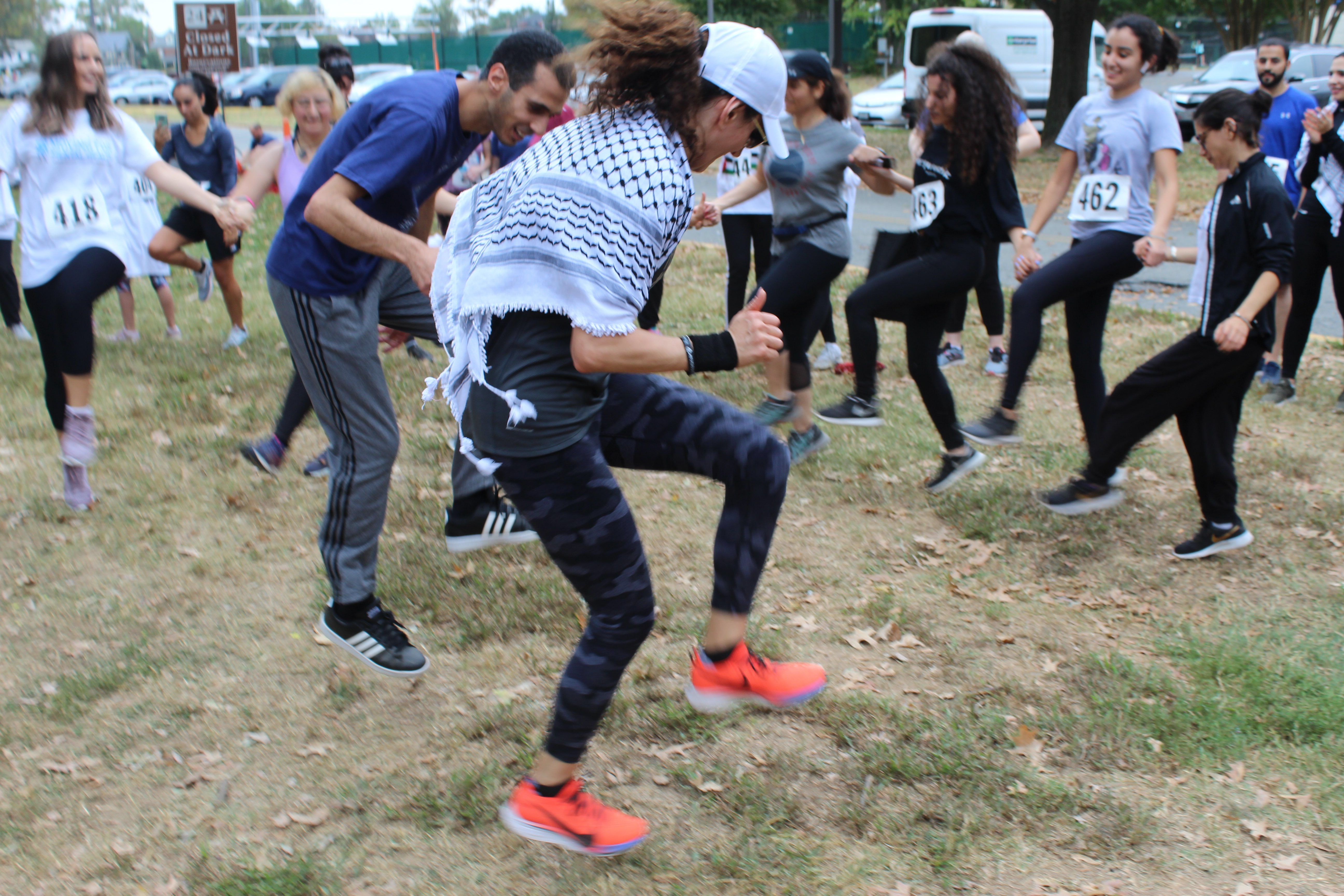 Two dancers take their dabka to another level after teaching beginners the basics at the Gaza 5k event (MEE/Sheren Khalel)