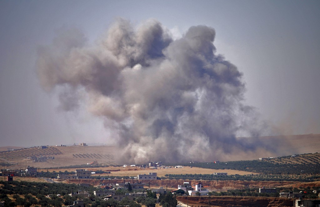 Smoke rises above the city of Daraa after regime air strikes in July 2018 (AFP)