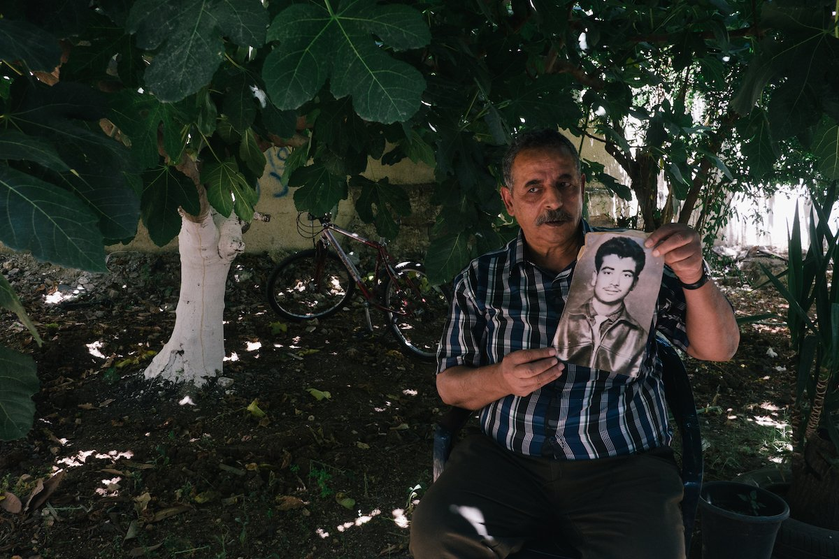 Hassan Dawleh holds a portrait of his brother Anis, who died in an Israeli prison