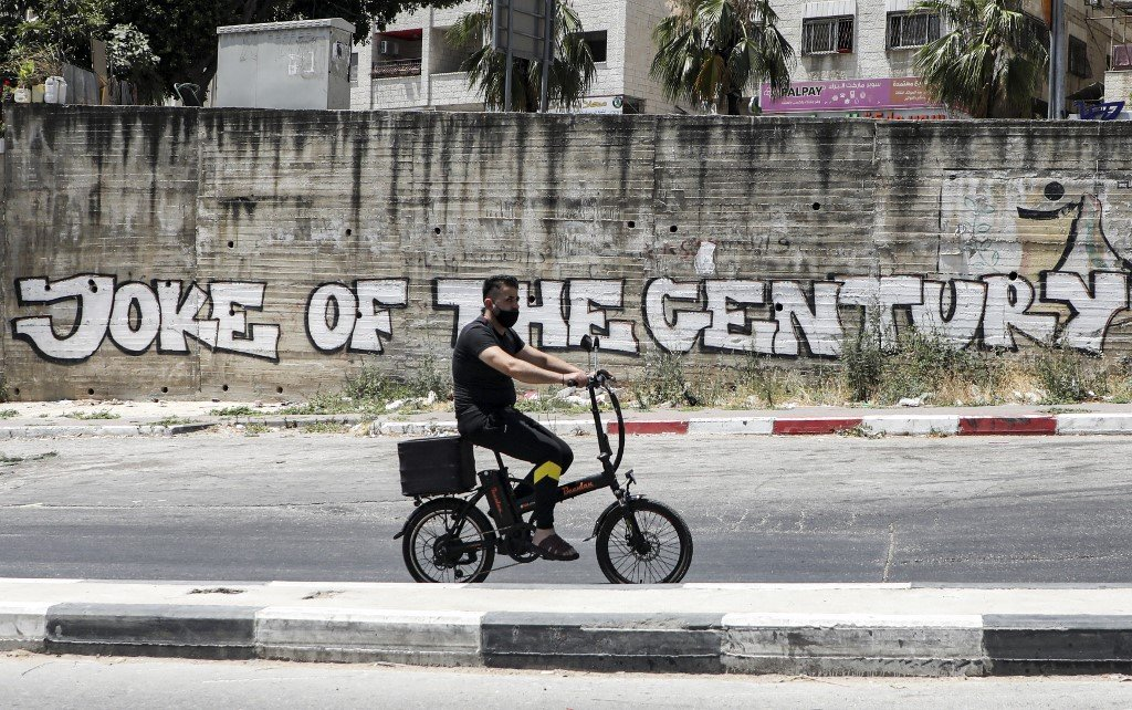 A mural in the occupied West Bank criticises the US 'deal of the century' on 2 July (AFP)