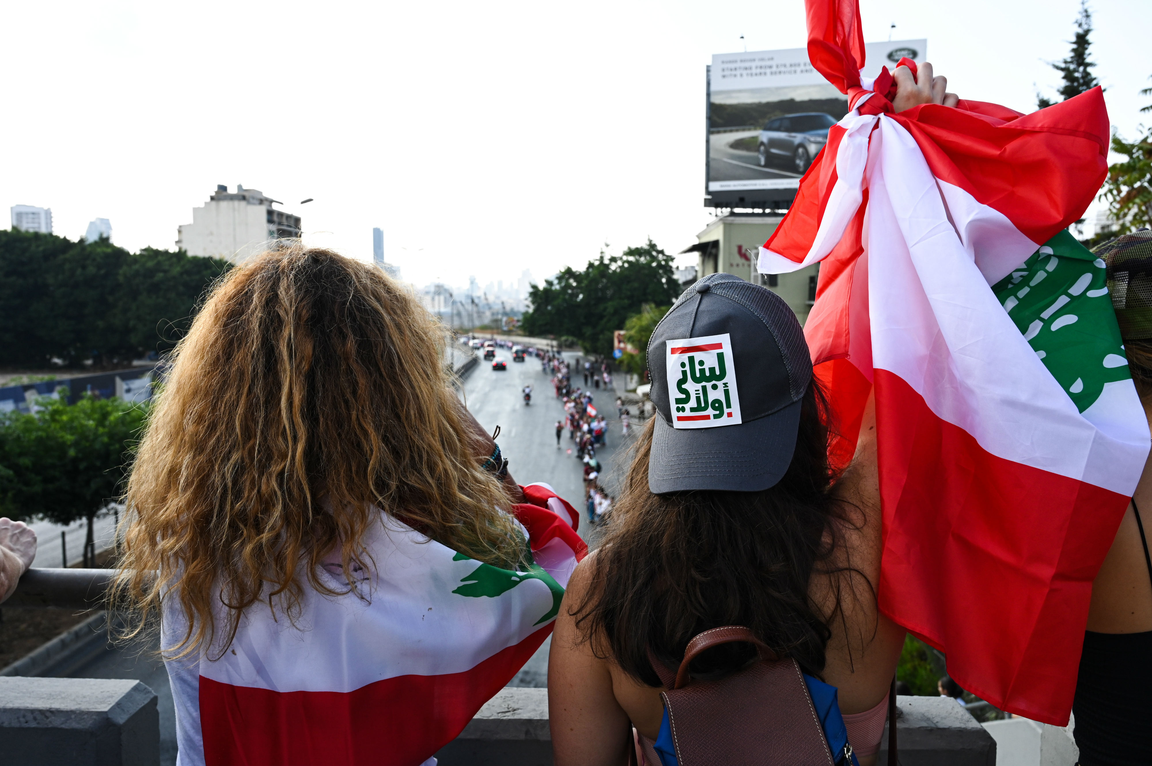"A woman, wearing a hat that reads ""Lebanese first"", raises a Lebanese flag as she looks down on the human chain from a bridge above the highway (MEE/Finbar Anderson)"