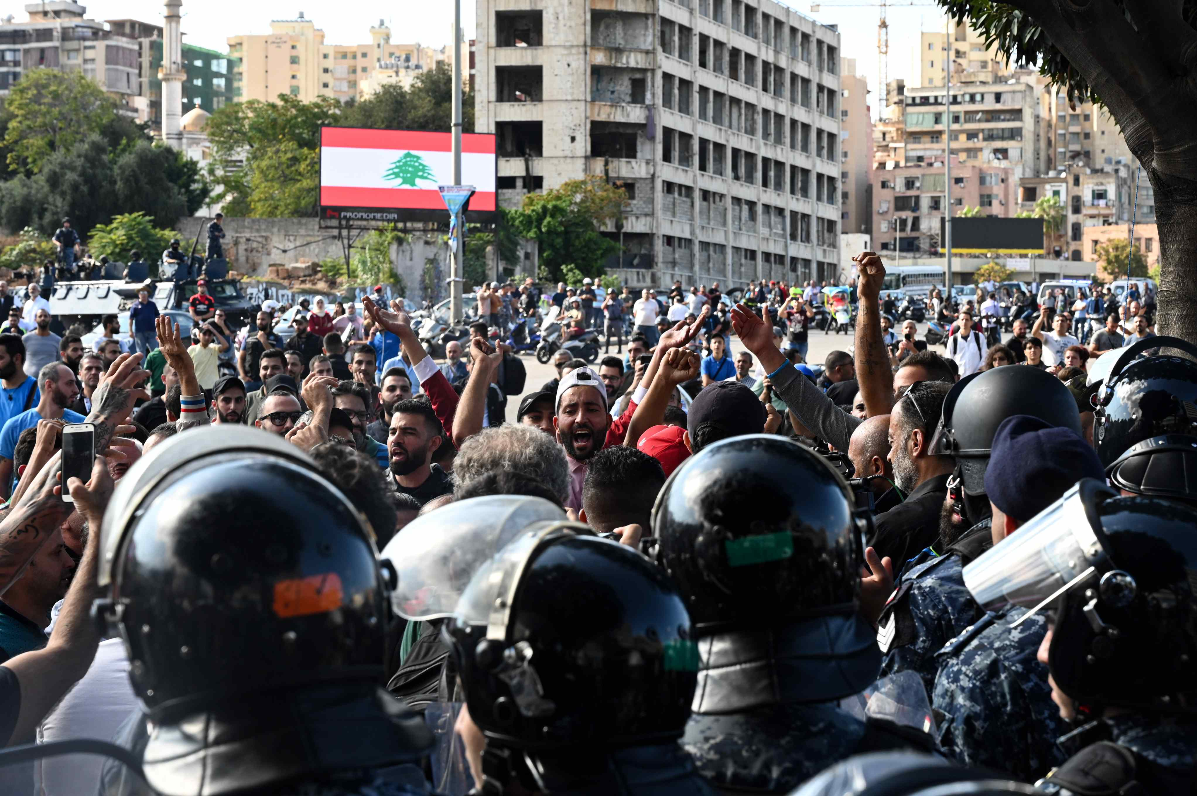 A group of young men, flanked by riot police, chants in support of Speaker of Parliament Nabih Berri (MEE/Finbar Anderson)