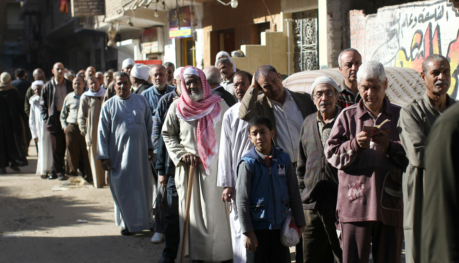 Egyptian men queue outside a polling station during the second round of a referendum on a new draft constitution in Giza, south of Cairo, on 22 December, 2012 (AFP)