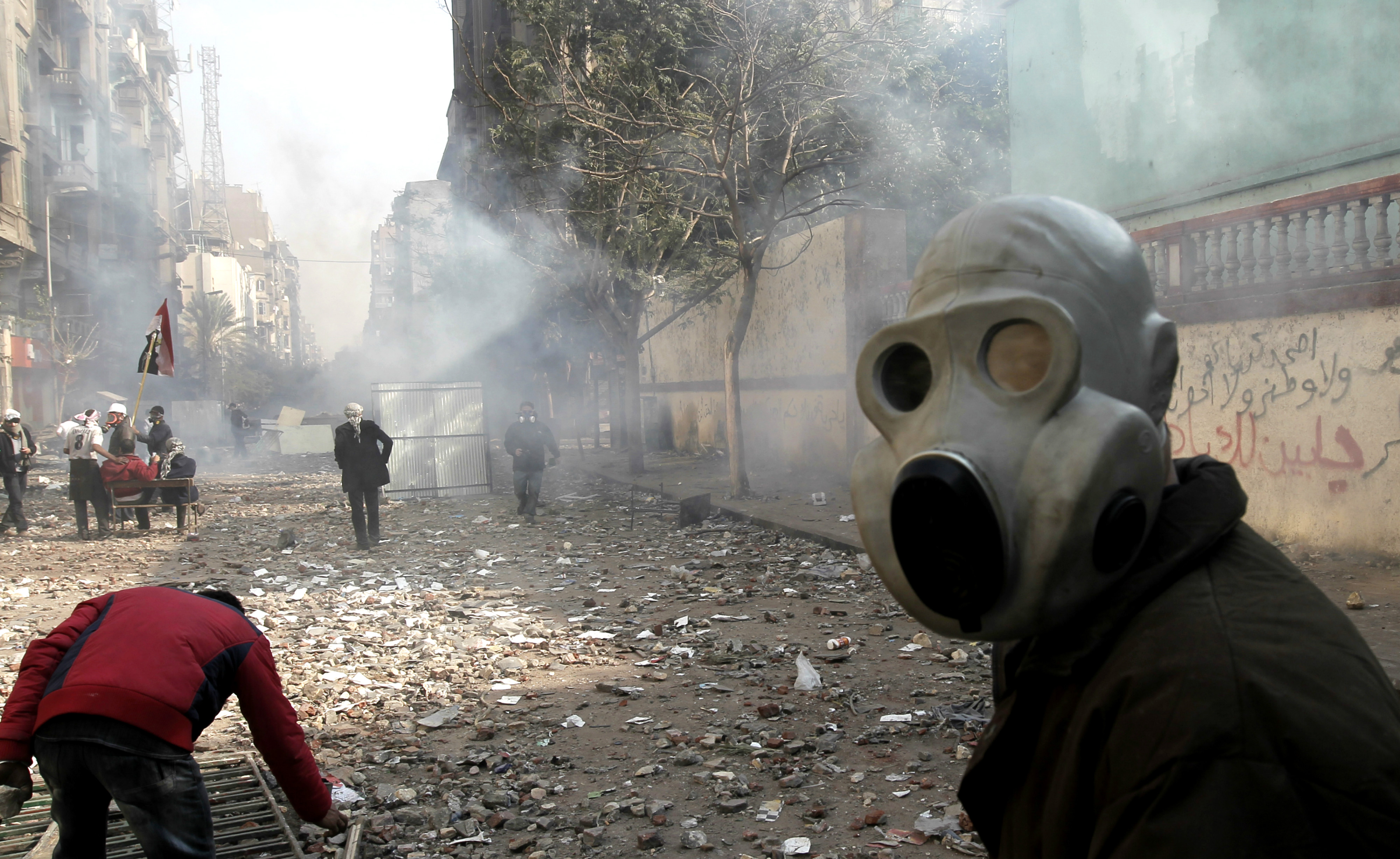 An Egyptian protester protects his face from tear gas during clashes with riot police near Tahrir Square, Cairo, in November 2011 (AFP)