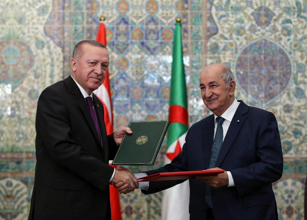 Erdogan and Algerian President Abdelmadjid Tebboune sign bilateral agreements in Algiers on 26 January (Murat Kula/Turkish Presidential Press Service/AFP)
