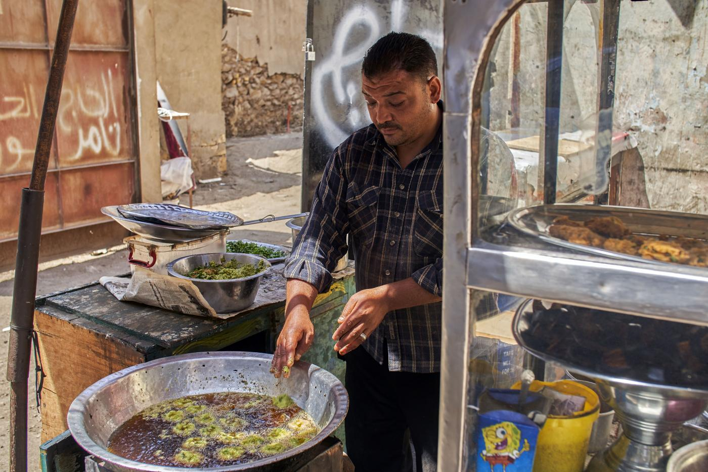 Sayed El Deeb, a vendor on Abd Al Aziz Gaweash street, whose family has been making taameya (falafel) for 50 years, in downtown Cairo, 10 April 2019 (MEE/Hamada Elrasam)