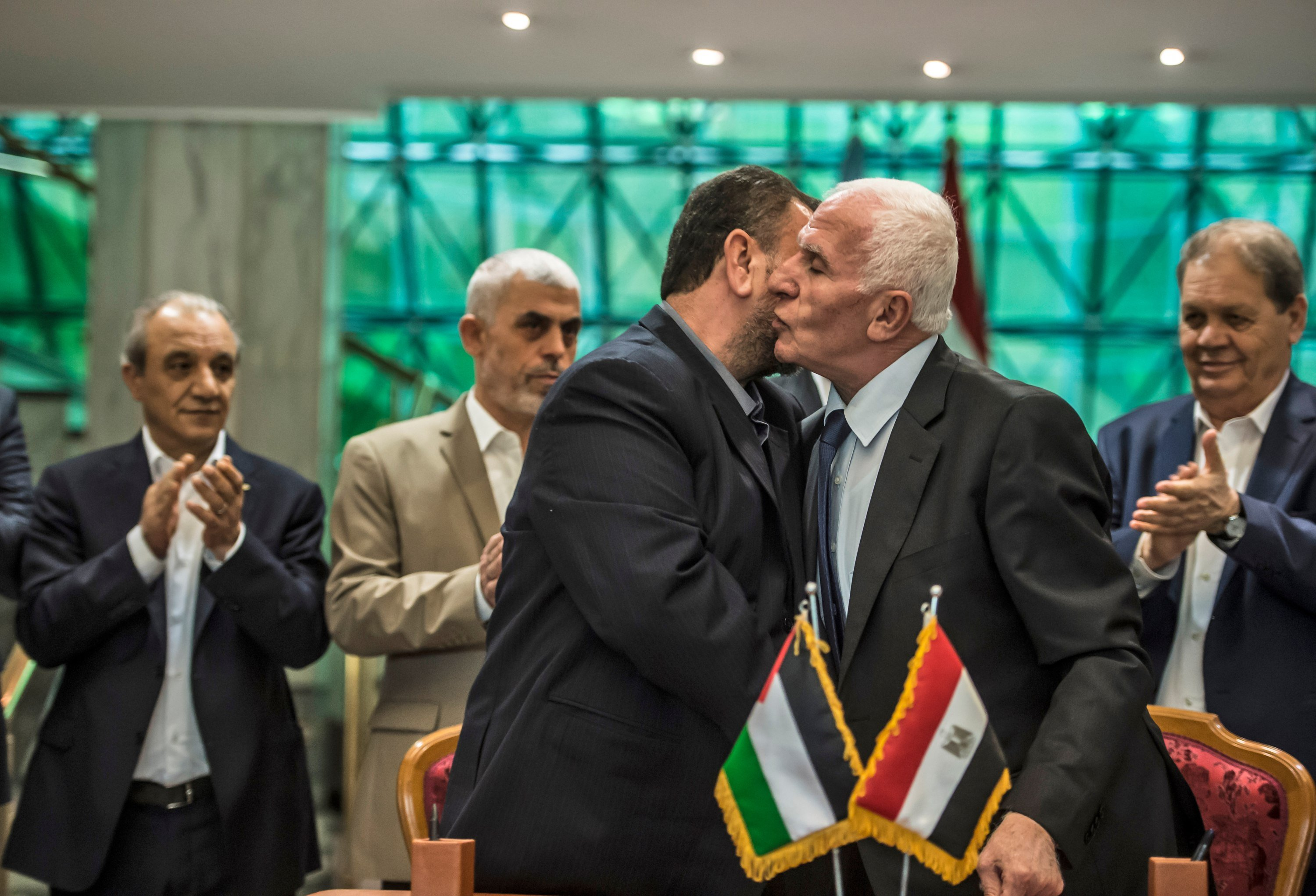 Fatah's Azzam al-Ahmad, right, and Saleh al-Aruri of Hamas kiss after signing a reconciliation deal in Cairo on 12 October 2017. The deal however failed to durably resolve the enmity between the two Palestinian parties (AFP)