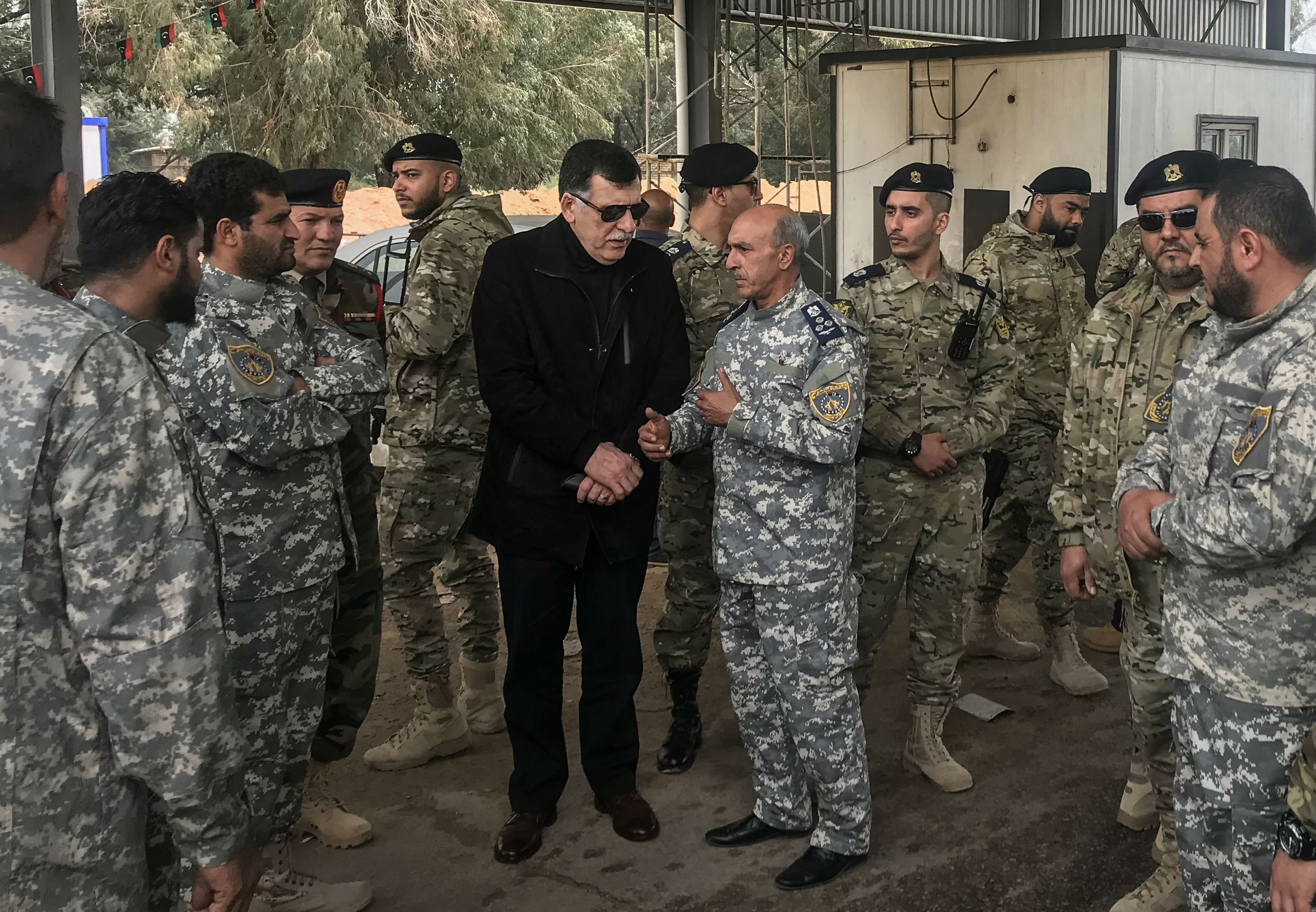Fayez al-Sarraj meets with military commanders who oversaw the retaking of the checkpoint (AFP)