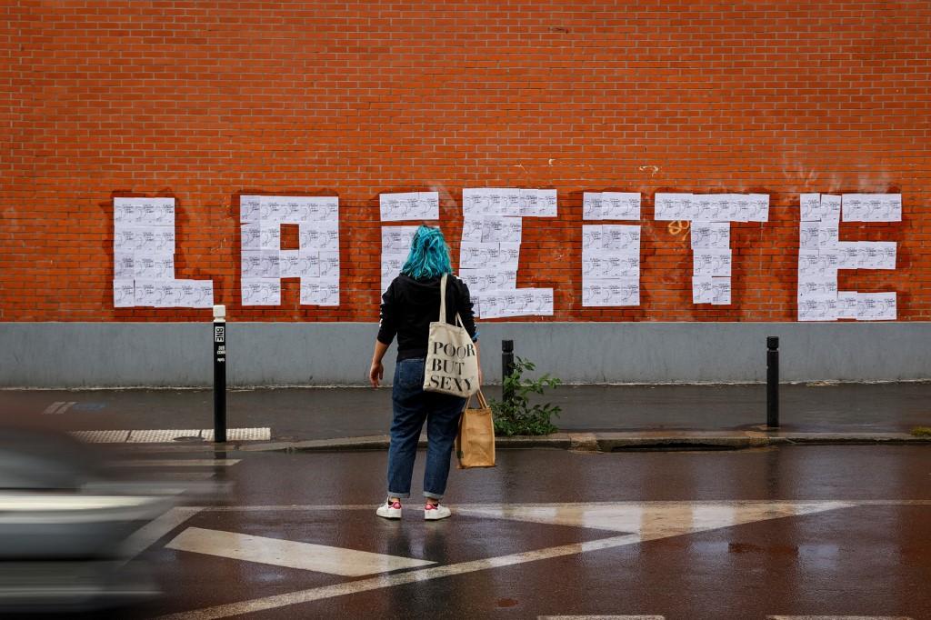 Une militante féministe regarde les affiches d'un dessin du dessinateur français Charb collées de manière à former le mot « laïcité », à Montreuil le 20 octobre 2020 (AFP)
