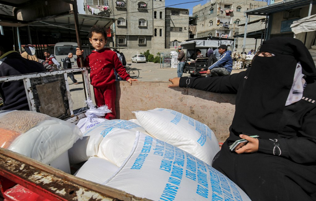 Palestinians receive UN food aid in Gaza's Khan Younis camp on 7 March (AFP)