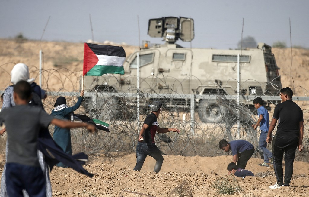 Palestinians confront Israeli security forces along the Gaza fence in 2019 (AFP)