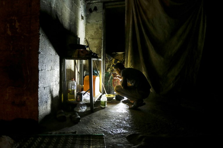 A Palestinian man eats during a power cut in Gaza City in September 2017 (AFP)