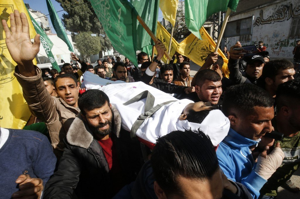 Mourners carry the body of a Palestinian teenager killed in Gaza on 30 November (AFP)
