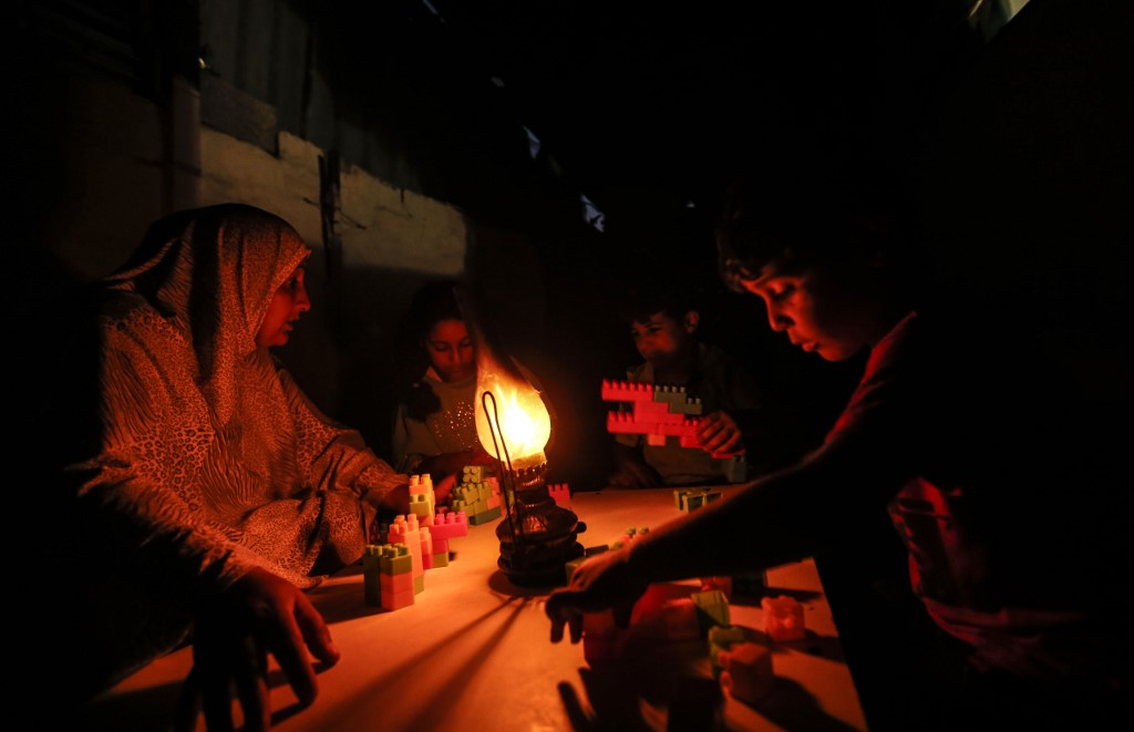 A Palestinian woman uses a gas lamp during a power cut in Gaza's Khan Younis refugee camp in July 2018 (AFP)