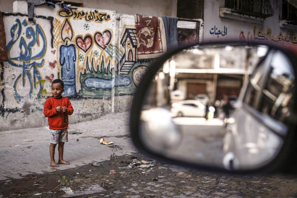A Palestinian boy stands near his home in al-Shati refugee camp in Gaza on 6 December (AFP)