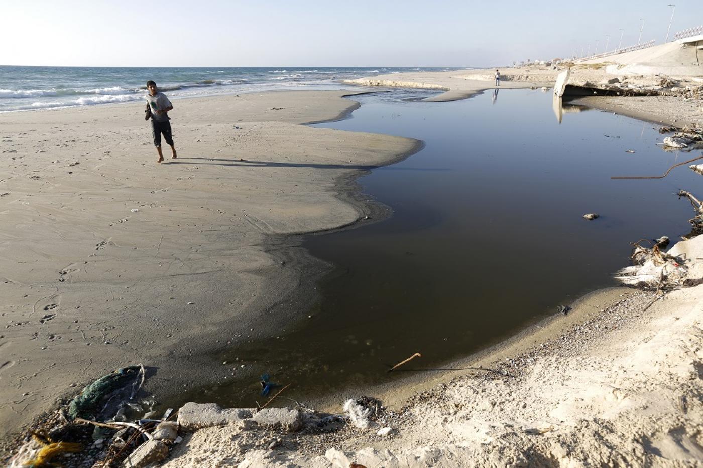 Un Palestinien passe devant des eaux usées déversées dans la mer sur une plage à proximité de Gaza (AFP)