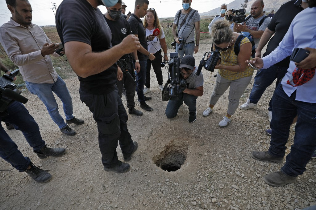 Полиция и журналисты собираются вокруг дыры, использованной шестью палестинцами для побега из тюрьмы Гильбоа на севере Израиля 6 сентября 2021 года (AFP)
