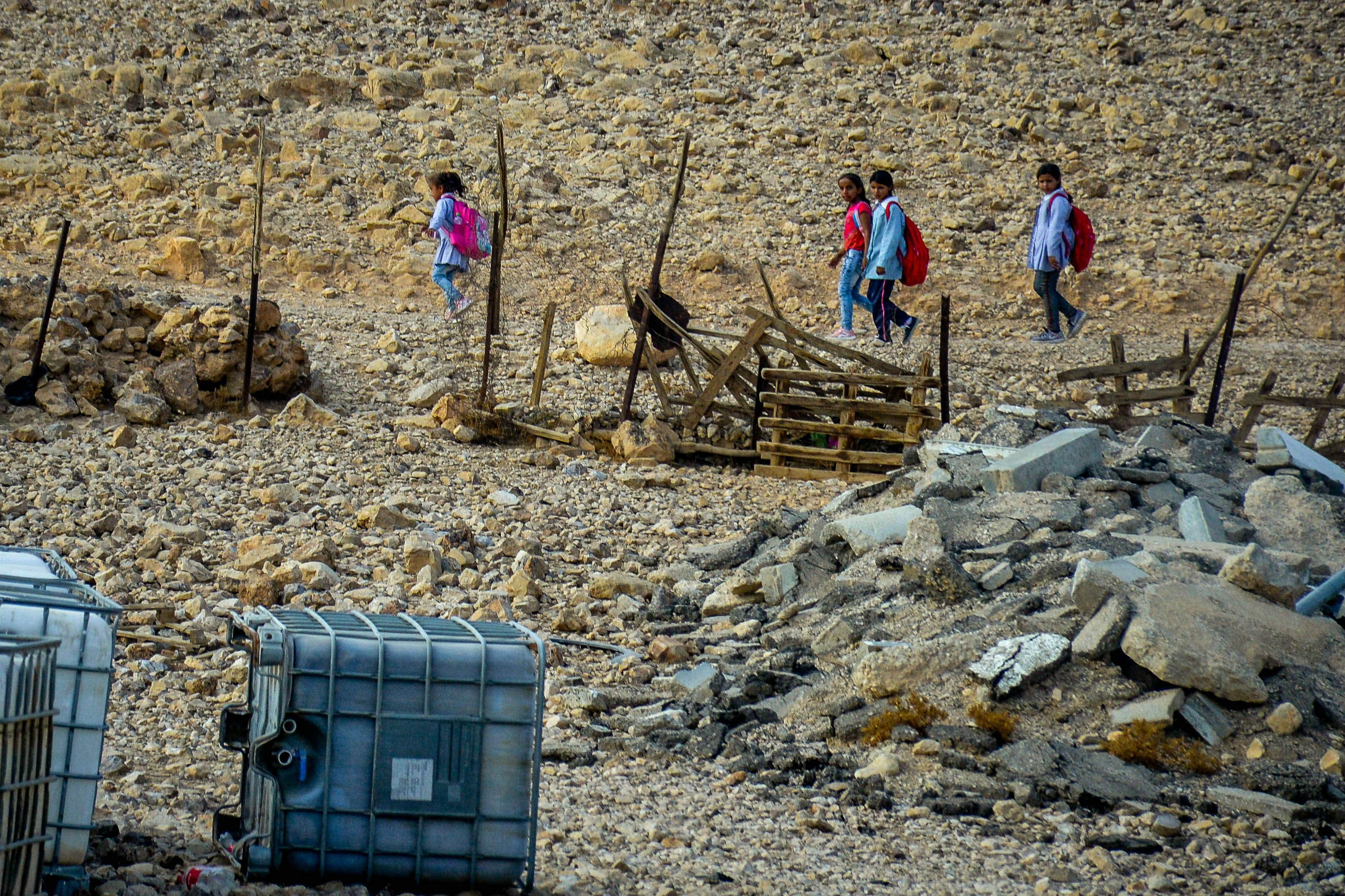 Palestinian school from the Al Awjah Bedouin community walk by empty water reserves (MEE/Qassam Muaddi)