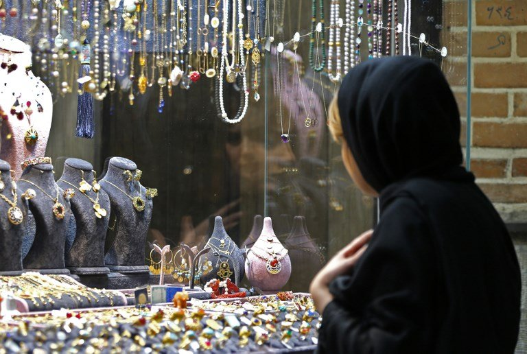 A woman glances at jewellery displayed in a shop widow in the Iranian capital Tehran's grand bazar on November 3, 2018.