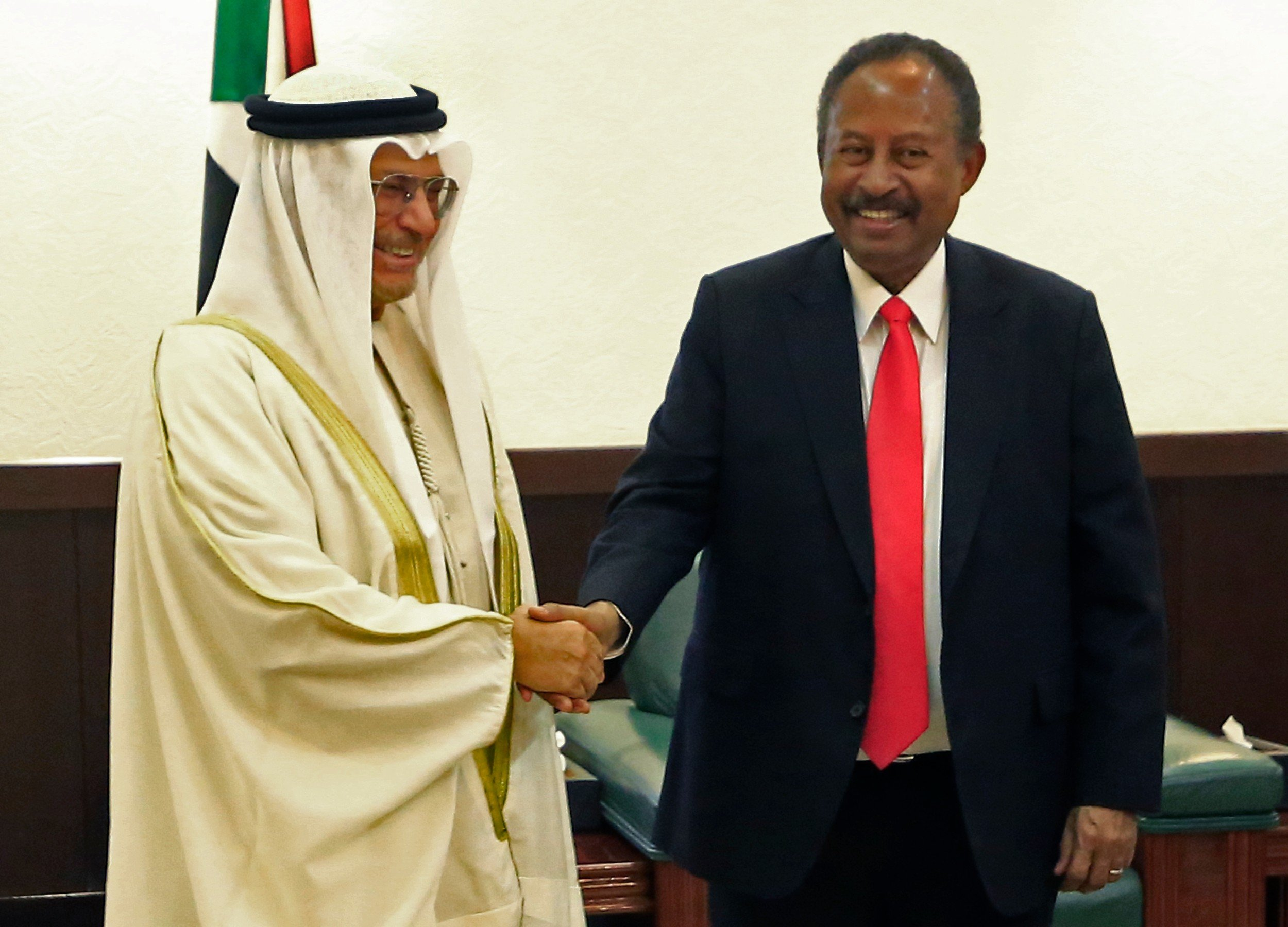 Sudan Prime Minister Abdalla Hamdok shakes hands with UAE Foreign Affairs Minister Anwar Gargash in Khartoum on 14 January. The UAE reportedly facilitated the Burhan-Netanyahu meeting (AFP)
