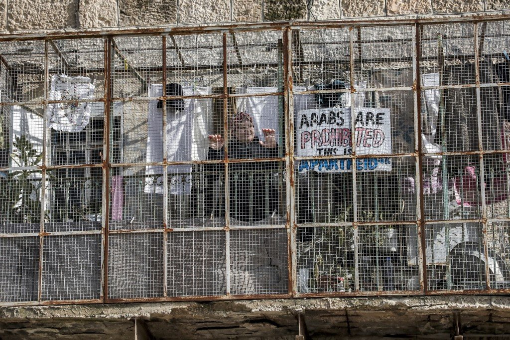 A sign reads 'Arabs are prohibited, this is Apartheid St' in Hebron on 28 January (AFP)