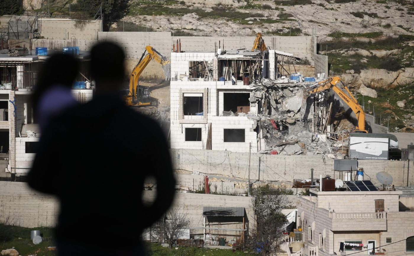 Des pelles hydrauliques démolissent un bâtiment palestinien au nord de la ville d'Hébron, en Cisjordanie occupée, en février 2018 (AFP)