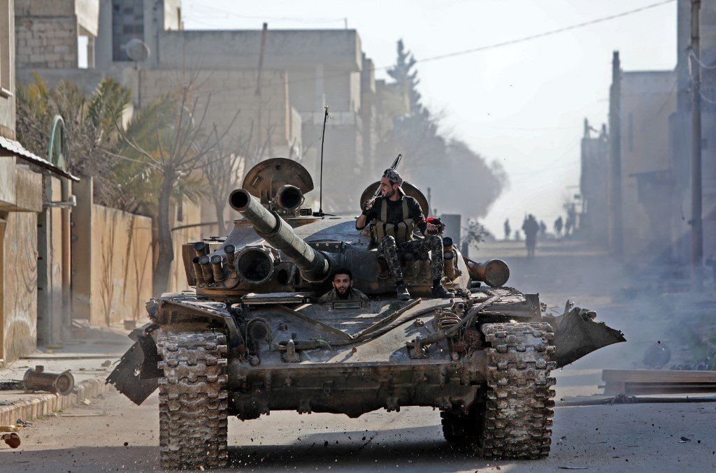 Syrian rebels ride a tank in eastern Idlib province on 27 February (AFP)