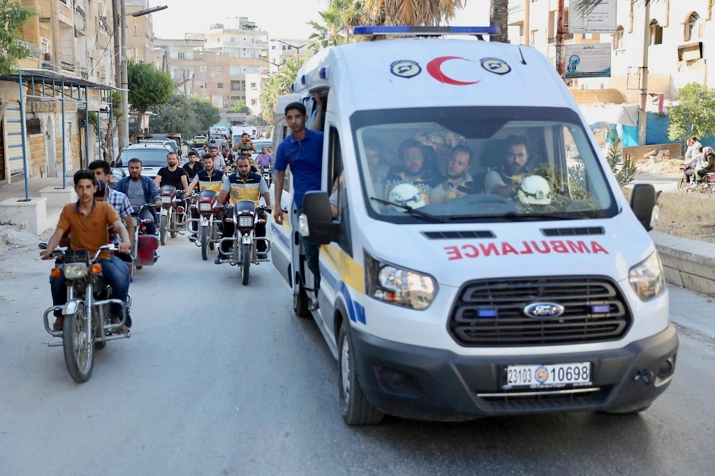 White Helmets and friends in funeral procession of citizen journalist Anas al-Dyab in Syria's Idlib on Sunday (AFP)