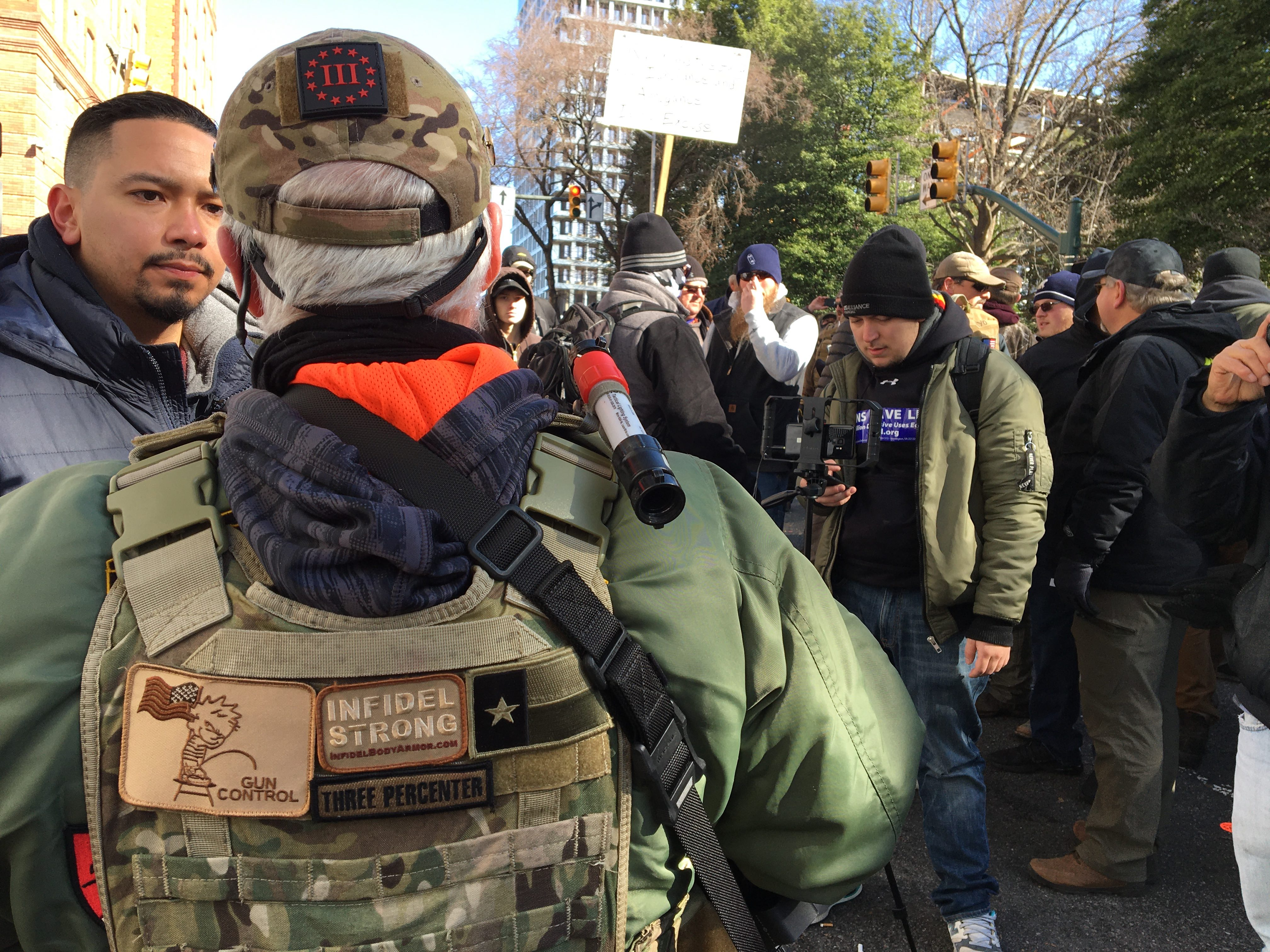 One protester in military garb wears patches with far-right III Percenter emblems on his vest and hat. (Sheren Khalel/MEE)