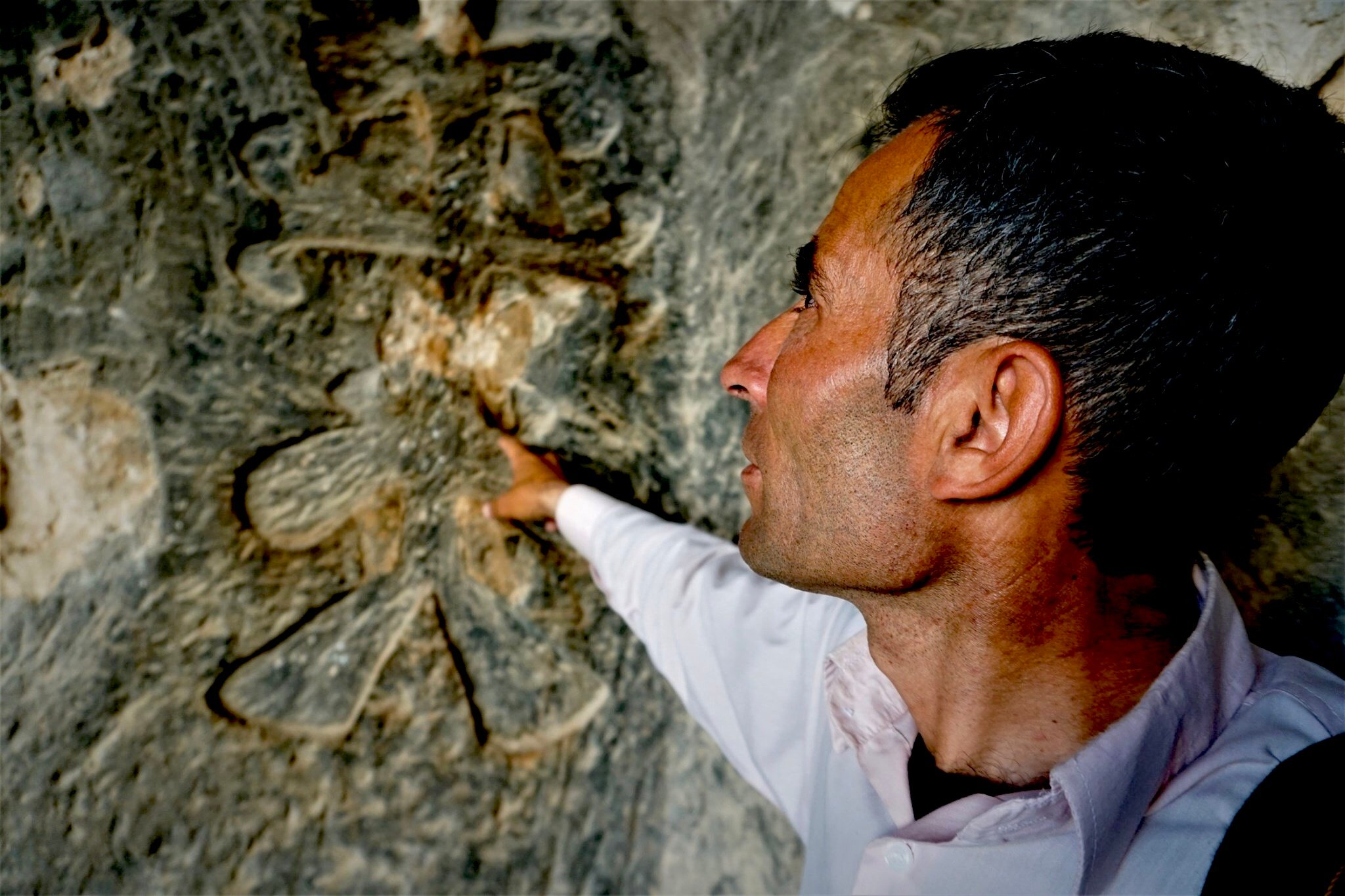 Shepherd Ali points to a leaf-like Christian cross carved on the wall inside one of the caves that would sink under the artificial lake. (Nimet KIRAC/ MEE)