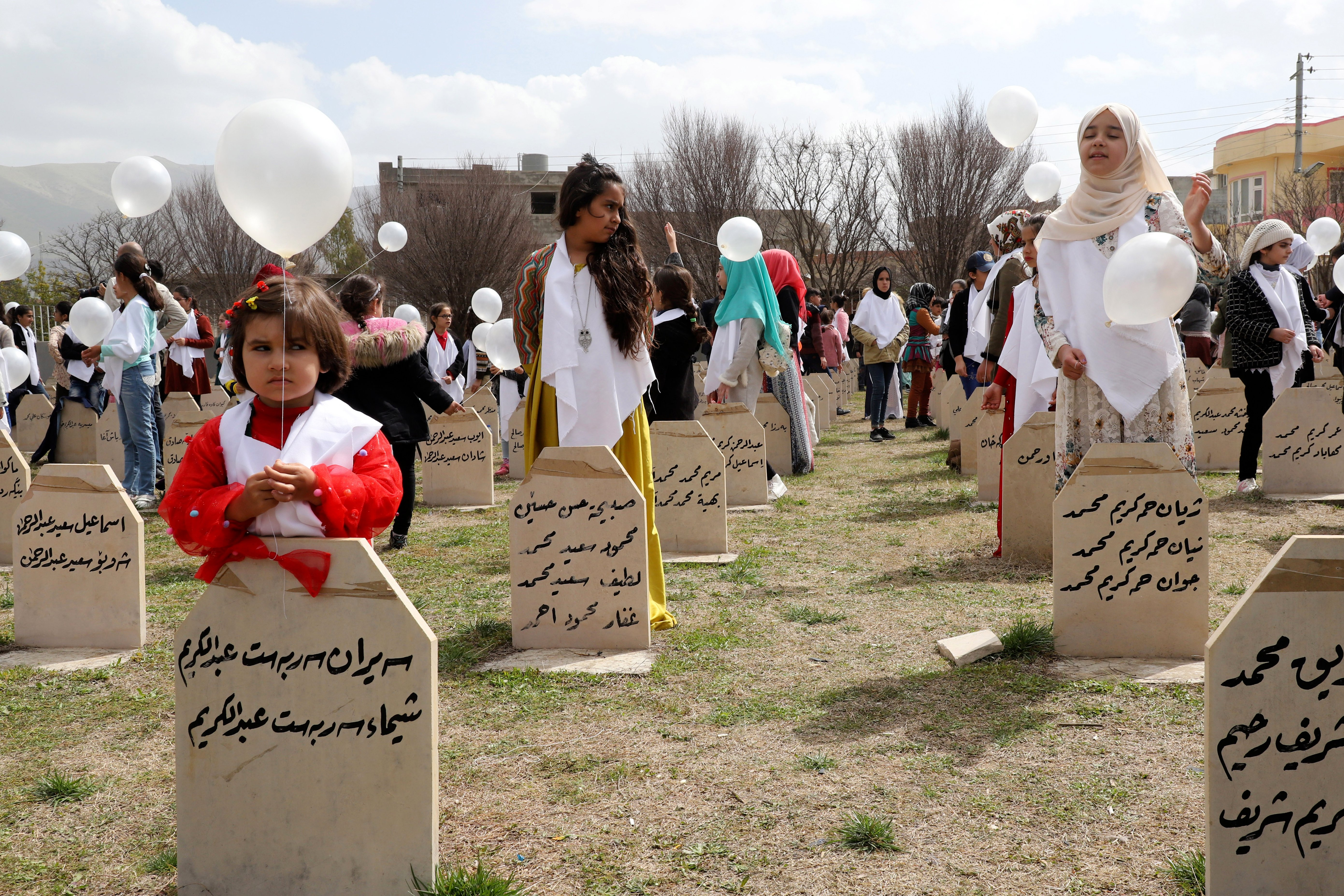 Iraqi-Kurds visit a grave site in Halabja near the monument for victims of the Halabja gas massacre that killed some 5,000 people as they mark the 31th anniversary of the attack (AFP)