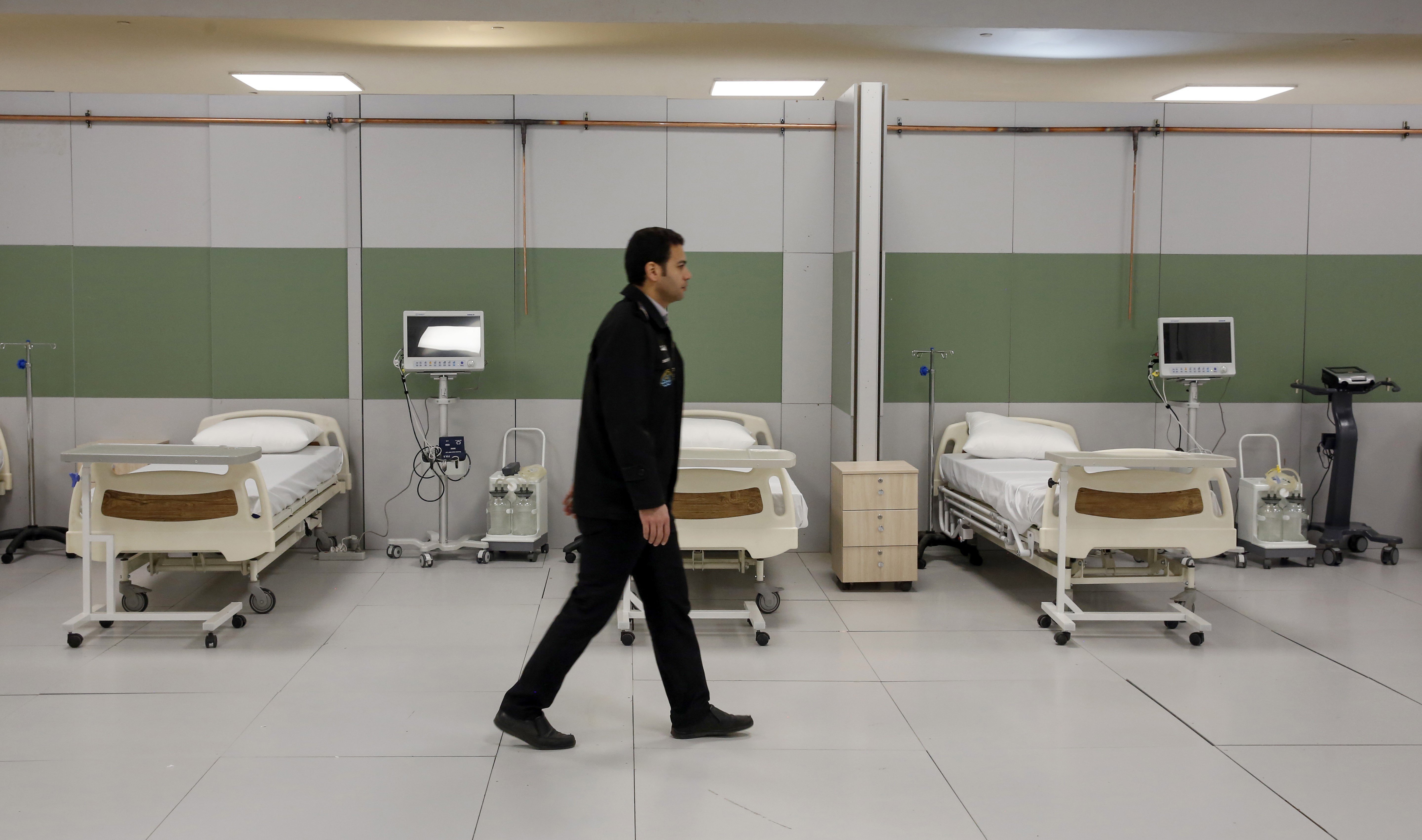An Iranian worker walks past beds at a makeshift hospital inside the Iran Mall, northwest of Tehran, on 21 March (AFP)