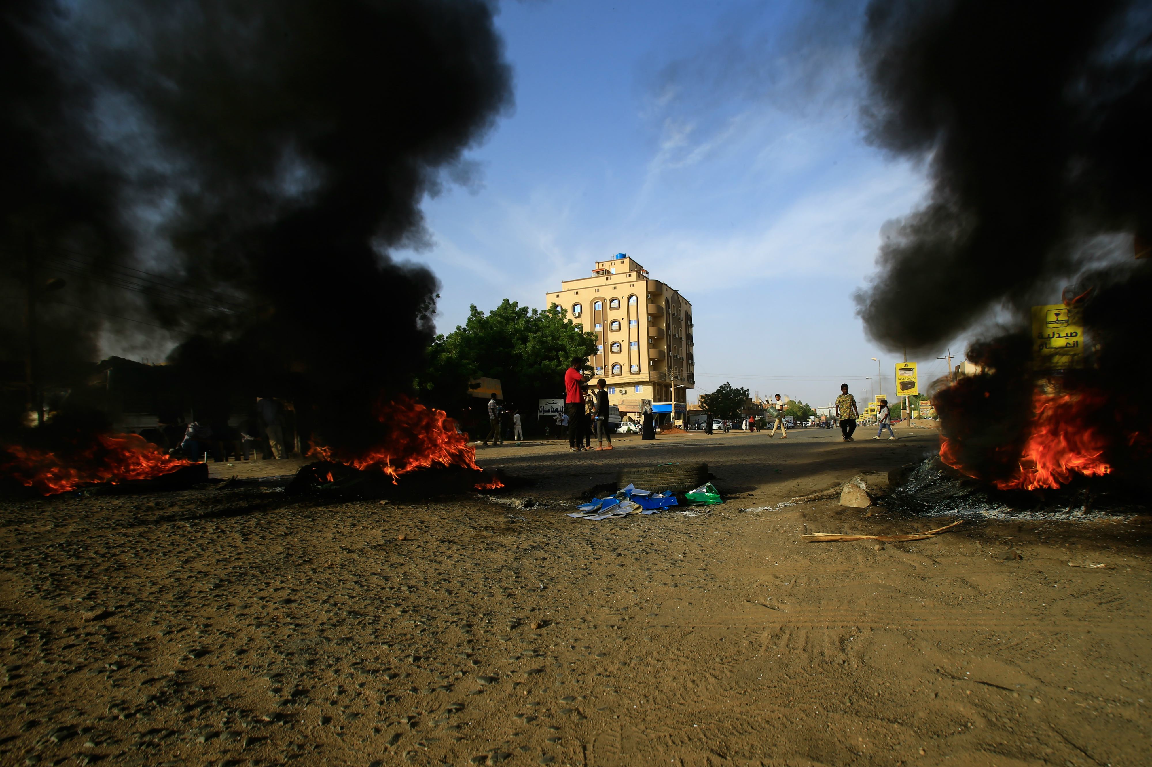 Demonstrators burn tires in the middle of a main street in Khartoum as they protest against the results of the probe into the June raid on a Khartoum protest camp (AFP)