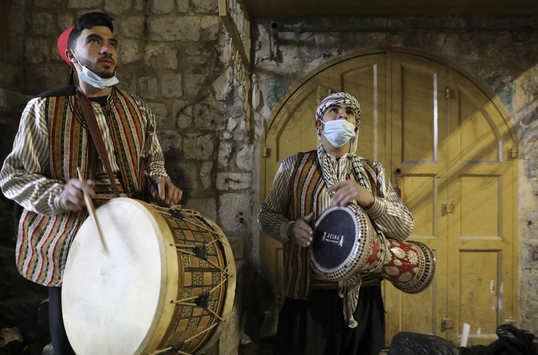 CISJORDANIE OCCUPÉE. Les musaharatis(batteurs du Ramadan), qui dans la tradition, réveillent les musulmans pour le repas traditionnel, le suhur, avant l'aube avant le début du jeûne du lendemain, font leur tournée dans la vieille ville d'Hébron, le 14 avril 2021 (AFP)